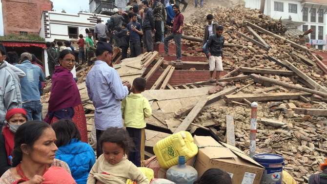 People survey a site damaged by an earthquake, in Kathmandu